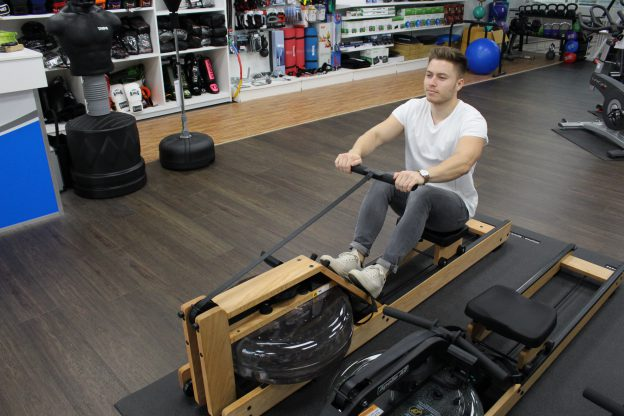 Sporter op de Waterrower roeitrainer