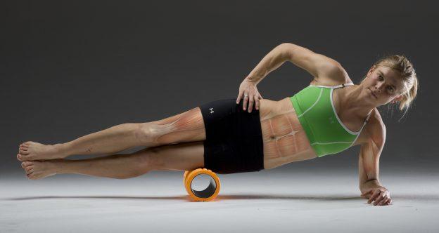 Vrouw met foam roller onder haar benen