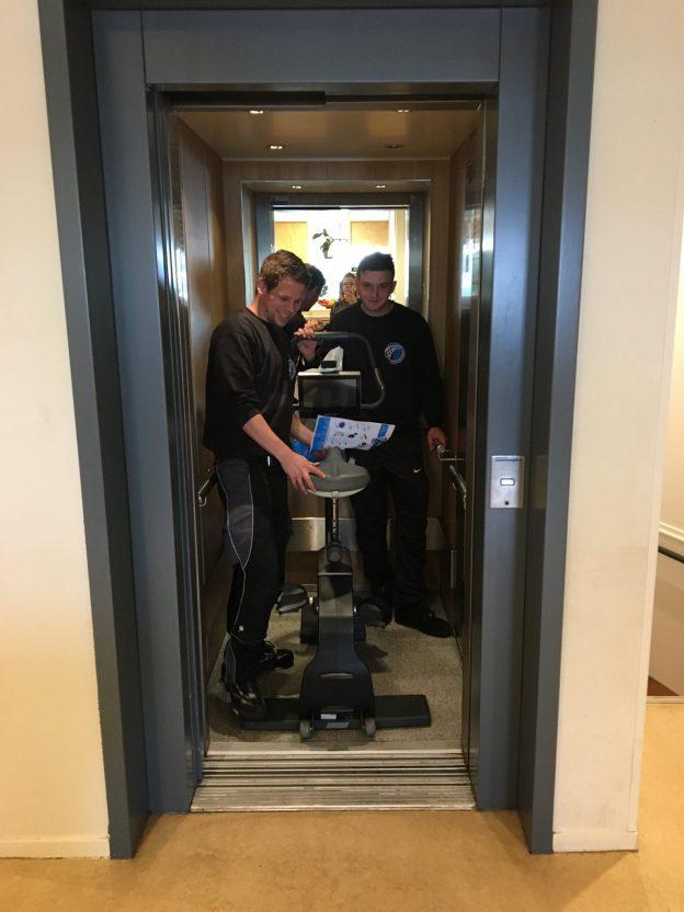 Bezorgers Fitshop in de lift met hometrainer