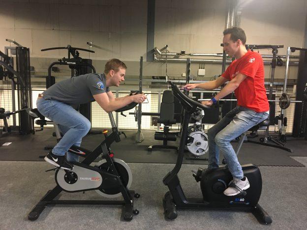 Hometrainer en spinningfiets tegenover elkaar